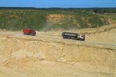 LKWs gehen unten in eine Grube hinter Sand Stockfotografie