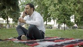 Llámeme en cualquier momento Hombre joven alegre que habla en el teléfono que se sienta en la hierba en el parque metrajes