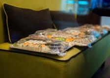 Llévese la comida asiática en las placas envueltas en la bolsa de plástico en el sofá imagen de archivo libre de regalías