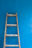 Lladder against blue wall Royalty Free Stock Photo