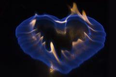 Llama azul en la forma del corazón que quema en superficie brillante Imágenes de archivo libres de regalías