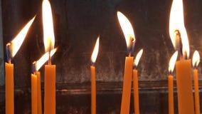 Llama de las velas ardiendo de la cera que agitan en el viento