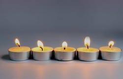Llama de vela en fondo gris Imagenes de archivo