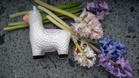 Llama money box near the window with flowers on white background. Selected focus, toned, copy space royalty free stock photos