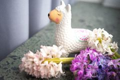 Llama money box near the window with flowers on white background. Selected focus, toned, copy space stock images