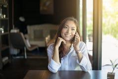 Llamada asiática de la mujer con el teléfono de célula mientras que se sienta solamente en c Imagen de archivo libre de regalías