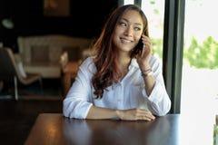 Llamada asiática de la mujer con el teléfono de célula mientras que se sienta solamente en c Fotos de archivo libres de regalías
