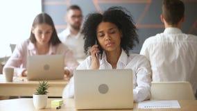 Llamada de contestación agujereada de la empresaria afroamericana usando el ordenador portátil en el lugar de trabajo de co-traba