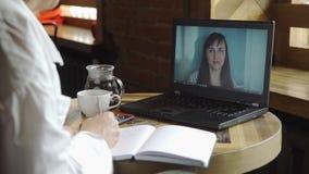 Llamada de la videoconferencia en el ordenador portátil en café almacen de video
