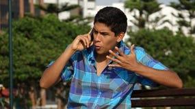 Llamada de teléfono adolescente enojada del muchacho Fotografía de archivo