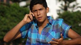 Llamada de teléfono confusa del muchacho adolescente Fotografía de archivo