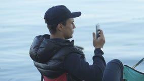 Llamada de teléfono de contestación del hombre durante la pesca, conexión pobre, calidad de la comunicación almacen de metraje de vídeo