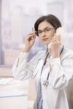 Llamada de teléfono de contestación del doctor joven Fotografía de archivo