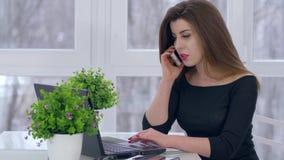Llamada de teléfono, mujer joven que habla en smartphone y que trabaja en el ordenador que se sienta en la tabla en sitio metrajes