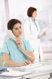 Llamada de teléfono que toma auxiliar para el médico Fotos de archivo