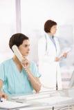 Llamada de teléfono que toma auxiliar, doctor en fondo Fotografía de archivo libre de regalías