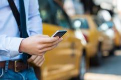Llamada de un taxi con el teléfono Foto de archivo libre de regalías
