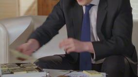 Llamada del acabamiento del hombre de negocios en el teléfono celular, poniendo tacos de dólares en la maleta metrajes