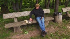 Llamada del hombre para jugar a ajedrez almacen de video