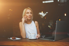 Llamada femenina atractiva con su teléfono de célula mientras que ella desayuna en cafetería imágenes de archivo libres de regalías