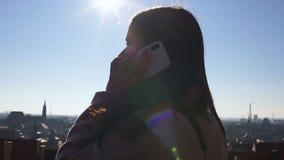 Llamada femenina del teléfono celular mientras que mira la ciudad europea del tejado, vagando por almacen de video