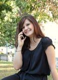 Llamada hermosa de la muchacha por el teléfono en un parque Foto de archivo