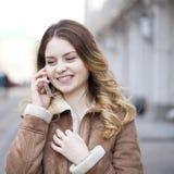 Llamada rubia joven hermosa por el teléfono Imagen de archivo libre de regalías