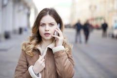 Llamada rubia joven hermosa por el teléfono Fotografía de archivo libre de regalías