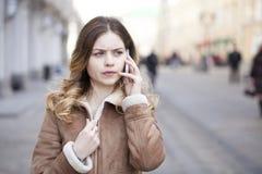 Llamada rubia joven hermosa por el teléfono Imágenes de archivo libres de regalías