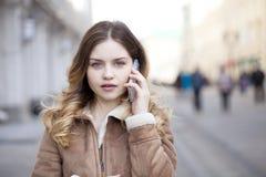 Llamada rubia joven hermosa por el teléfono Foto de archivo