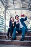 Llamada video asiática del hombre de negocios y de la empresaria a su amigo por smartphone imagenes de archivo