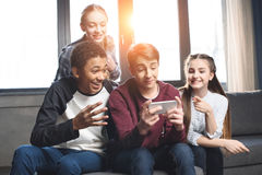 Llamada video del grupo multicultural feliz de los adolescentes con smartphone y sentarse en el sofá en casa Fotografía de archivo