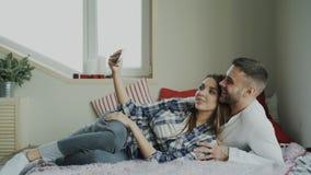 Llamada video que habla alegre de los pares lindos y cariñosos usando cámara del smartphone y charla con los padres que mienten e imagen de archivo