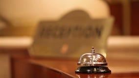 Llamadas del niño en la campana vieja del hotel en un soporte de madera