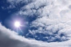 Llamarada brillante de la luz del sol en el cielo azul nublado fotografía de archivo libre de regalías