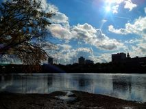 Llamarada brillante de Sun sobre un horizonte del edificio de New Jersey por el Riverbank de Raritan foto de archivo