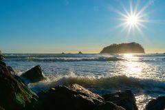 Llamarada de la lente, aturdiendo sobre el borde costero rocoso imagen de archivo