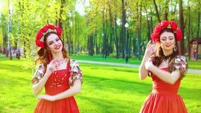 Llamarada de la lente en dos bailarines de sexo femenino en los trajes brillantes que realizan danza popular almacen de metraje de vídeo