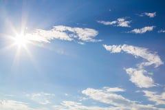 Llamarada de la lente y rayos naturales de la radiación en cielo azul con las nubes Imagen de archivo