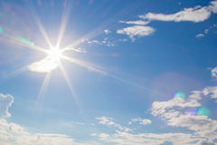 Llamarada de la lente y rayos naturales de la radiación en cielo azul con las nubes Fotografía de archivo libre de regalías