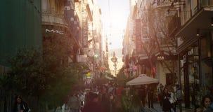 Llamarada de la puesta del sol en la calle de Ermou con la muchedumbre de la gente de los clientes almacen de metraje de vídeo