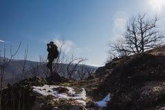 Llamaradas del cielo azul y del sol detrás de un caminante que se coloca en el top de la montaña imagen de archivo libre de regalías