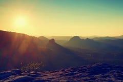 Llamaradas soleadas en lense Alba colorida Brumoso despertando en las colinas hermosas Los picos de colinas se están pegando haci Foto de archivo