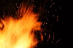 Llamas amarillas salvajes de un fuego de madera ardiente en la noche Foto de archivo libre de regalías