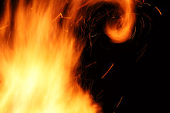 Llamas amarillas salvajes de un fuego de madera ardiente en la noche Foto de archivo