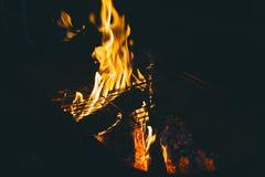 Llamas brillantes y carbones calientes en la noche Foto de archivo