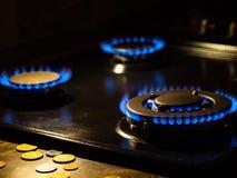 Llamas de la estufa de gas en la oscuridad con las monedas en el primero plano imagen de archivo