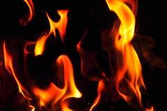 Llamas del fuego en un fondo negro Textura de la llama del fuego del resplandor detrás Imagen de archivo libre de regalías