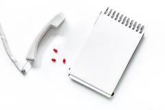 Llame al doctor por el teléfono en la composición blanca aislada de la opinión superior del fondo con el cuaderno y las píldoras  Fotos de archivo libres de regalías
