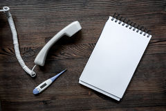 Llame por teléfono al microteléfono, al termómetro y al cuaderno en mofa de escritorio de madera oscura del doctor de la llamada  Imagenes de archivo